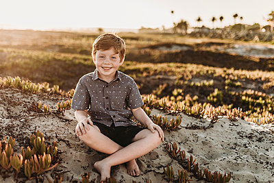 Portrait of young redheaded boy with freckles sitting and smiling - p1166m2136574 by Cavan Images