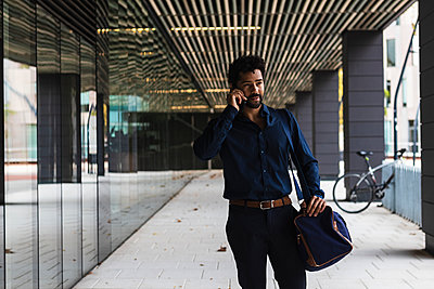 Contemplating entrepreneur with bag talking on smart phone in city - p300m2227134 by NOVELLIMAGE