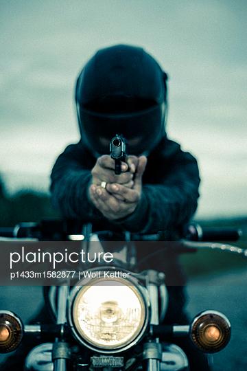 Man wearing crash helmet on a vintage 1980s motorbike,  pointing a handgun - p1433m1582877 by Wolf Kettler