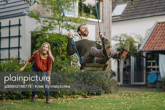 Woman pushing man, sitting on swing in garden - p300m2166715 von Kniel Synnatzschke