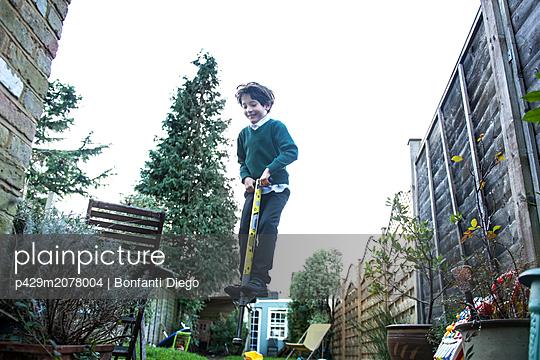 Boy jumping on pogo stick in garden - p429m2078004 by Bonfanti Diego