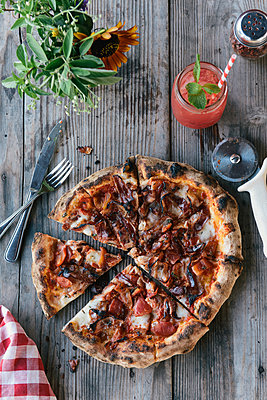 Sliced pizza served from the oven on picnic table outdoors on farm - p1166m2191966 by Cavan Images