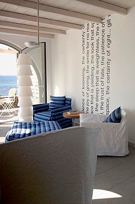 Various armchairs with loose covers and designer standard lamp in Mediterranean interior with sea view - p1183m997556 by Del Olmo, Henri