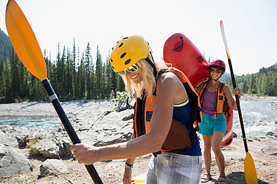 Women carrying kayak and paddles on craggy riverside - p1192m1063908f by Hero Images