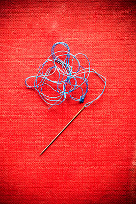 Needle and blue thread on a red background - p1302m2122522 by Richard Nixon