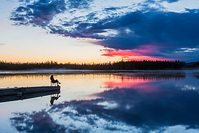 Woman relaxes at sunset at the edge of a dock at Chena River Lakes near Fox, Interior Alaska - p442m1086820 by Michael DeYoung