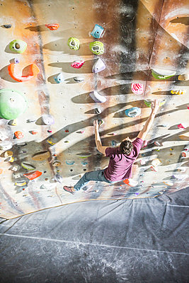 High angle view of athlete climbing rock wall in gym - p555m1411951 by John Fedele