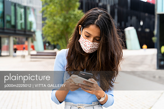 Woman wearing protective face mask while using smart phone in city during COVID-19 pandemic - p300m2225012 by VITTA GALLERY
