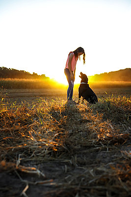 Teenage Girl and her Dog at sunset - p1019m1487240 by Stephen Carroll