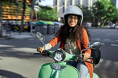 Smiling woman riding electric motor scooter in city during sunny day - p300m2227303 by Veam