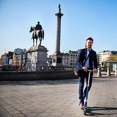 Businessman on scooter, Trafalgar Square, London, UK - p429m1417999 by Bonfanti Diego