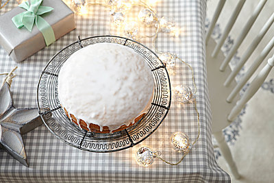 Iced cake on table with decorative lights - p429m1561610 by Debby Lewis-Harrison