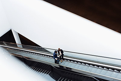 Businessman and businesswoman with wheeled luggage on escalator in hotel building - p429m2200742 by Sofie Delauw