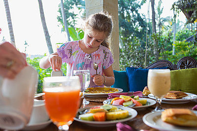 Caucasian girl enjoying breakfast on patio - p555m1419362 by Marc Romanelli