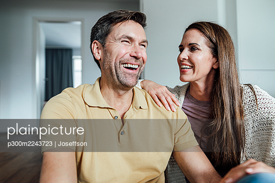 Mature man laughing while woman looking at him in apartment - p300m2243723 by Joseffson
