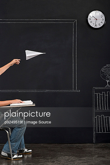 A boy throwing a paper airplane - p9249519f by Image Source