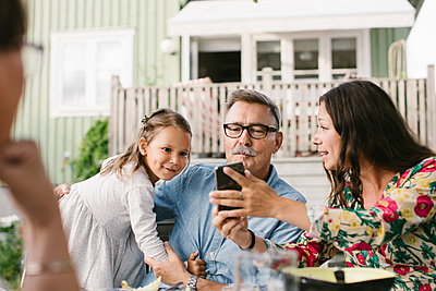 Mid adult woman showing mobile phone to family while sitting in backyard - p426m2036514 by Maskot