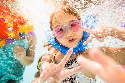 Caucasian children swimming underwater in swimming pool - p555m1411529 by John Fedele
