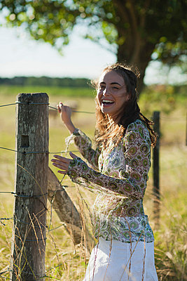 Young woman standing by fence in field - p624m710980f by Laurence Mouton