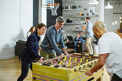 Business people playing foosball in office - p1166m1423452 by Cavan Images