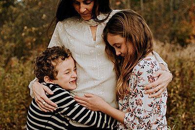 Side view of happy siblings with mother at park - p1166m1555656 by Cavan Images