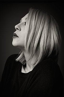 Profile portrait of a blonde woman in black and white - p1619m2191635 by Laurent MOULAGER