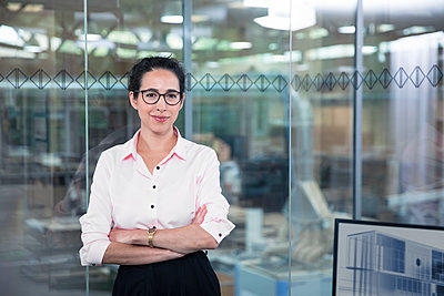 Confident female entrepreneur leaning on glass wall at office - p300m2266049 by Florian Küttler