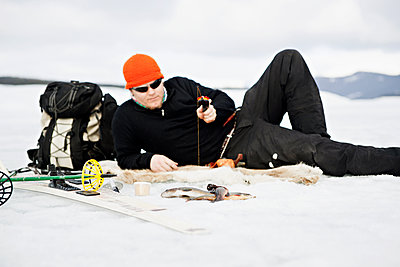 Man lying on snow and fishing - p312m1551903 by Johner Images