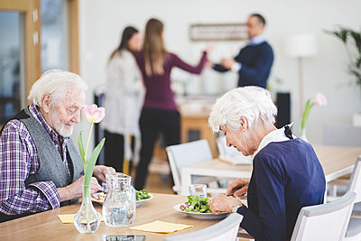 Senior couple eating lunch while at table in nursing home - p426m2018662 by Maskot