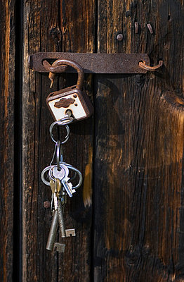 Close-up of barn door with padlock and bunch of keys hanging - p5756830f by Berit Djuse