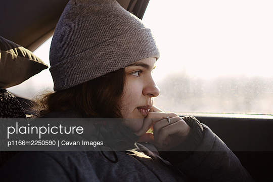 A girl in gray clothes looks out the car window, leans on her hand. - p1166m2250590 by Cavan Images