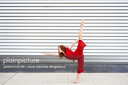 Sporty young woman doing acrobatics outdoors - p300m2140189 by Javier Sánchez Mingorance