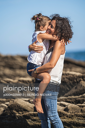 Mother embracing daughter while standing on flysch against sky - p300m2256613 by SERGIO NIEVAS
