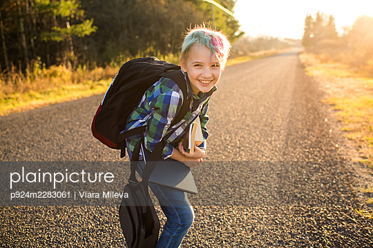 Canada, Ontario, Smiling boy with books on rural road at sunset - p924m2283061 by Viara Mileva