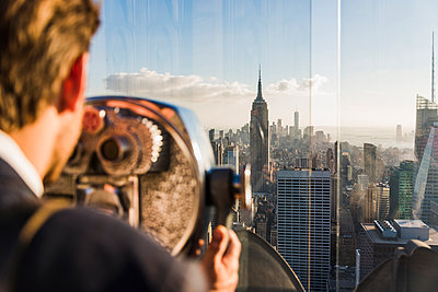 USA, New York City, man looking through coin-operated binoculars on Rockefeller Center observation deck - p300m2013080 by Uwe Umstätter