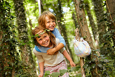Girl carrying boy piggyback in forest - p300m2180120 by Stefanie Aumiller