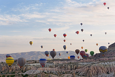 Turkey, Eastern Anatolia, Cappadocia, hot air balloons hoovering over tuff rock formations at Goereme National Park - p300m949064 by Martin Siepmann