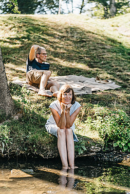 Happy couple relaxing on the riverbank - p586m1172023 by Kniel Synnatzschke