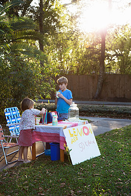 Boy and sister drinking lemonade from lemonade stand in garden - p924m1446892 by Kinzie Riehm