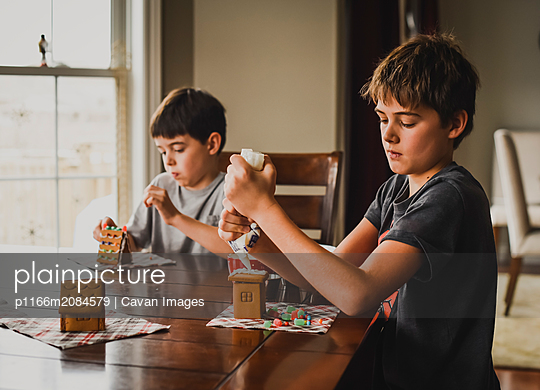 Two young boys decorating gingerbread houses together at the table. - p1166m2084579 by Cavan Images