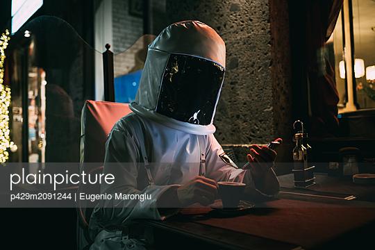 Astronaut using smartphone at sidewalk cafe - p429m2091244 by Eugenio Marongiu
