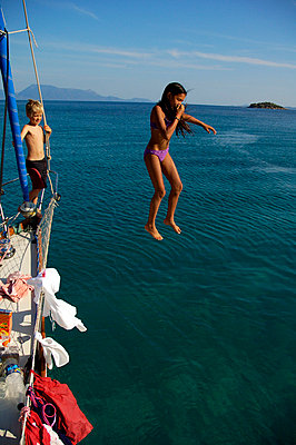 Boy watching a girl jump into the water from a boat - p1025m779997f by Björn Andrén