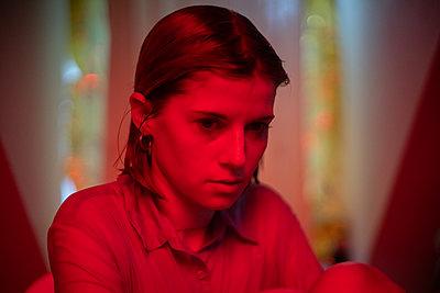 Junge Frau in rotem Licht - p1321m2141717 von Gordon Spooner