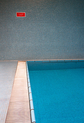 Empty indoor swimming pool with sign at the wall - p300m1115072f by Wolfgang Weinhäupl