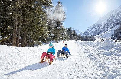 Couple sledding in sw-covered landscape - p300m1587085 by Christian Vorhofer