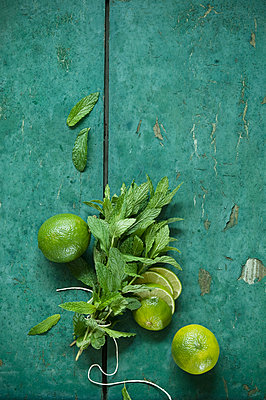 Bunch of mint and limes on rustic wooden background - p300m2059863 by Achim Sass