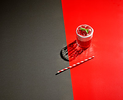 High angle view of pomegranate drink on colored background - p300m2143966 by Kai Schwabe
