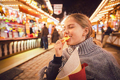 Young girl eating potato chip at carnival in city during night. Munich, Germany - p300m2197739 by Studio 27