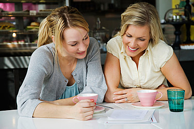 Two women having a business meeting and a cup of coffee in a café Sweden. - p31220874f by AMe Photo
