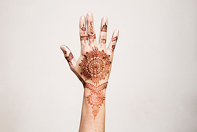 Hand with henna tattoo making gesture - p429m2075435 by Tom Dunkley